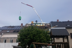 Kran hebt Material hinter Haus in Plauen